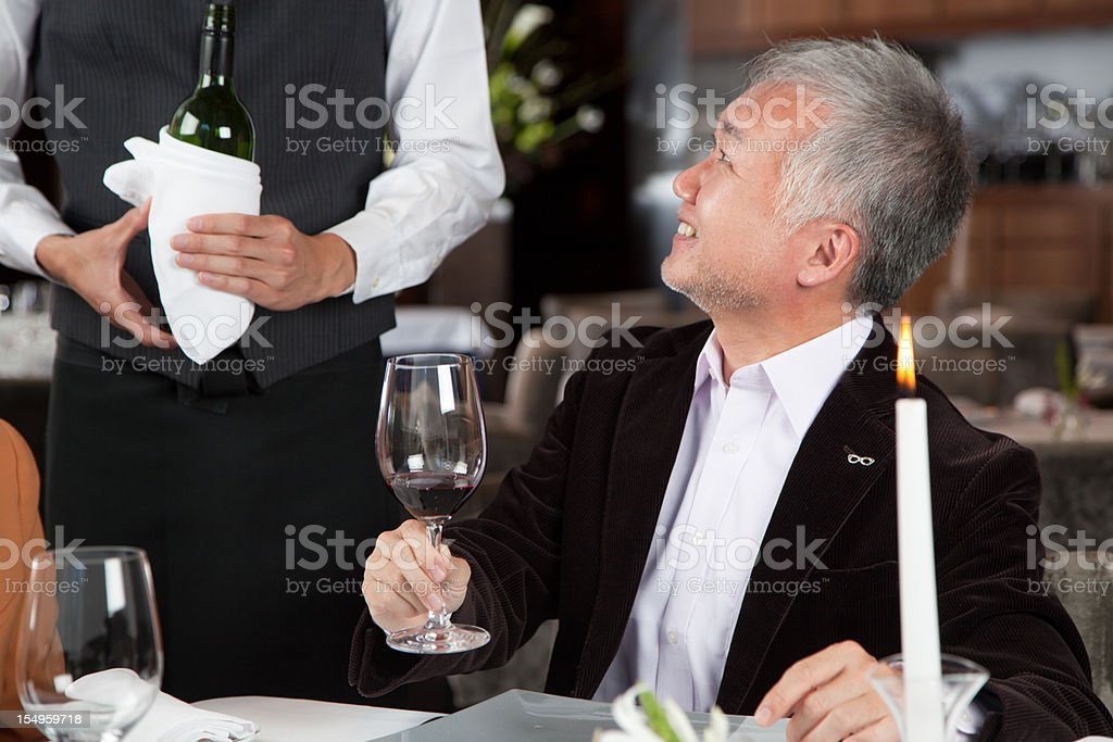 Mature Japaneese restaurant guest testing red wine. royalty-free stock photo