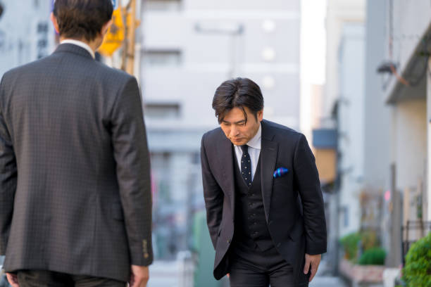 Mature Japanese businessman bowing to show respect stock photo