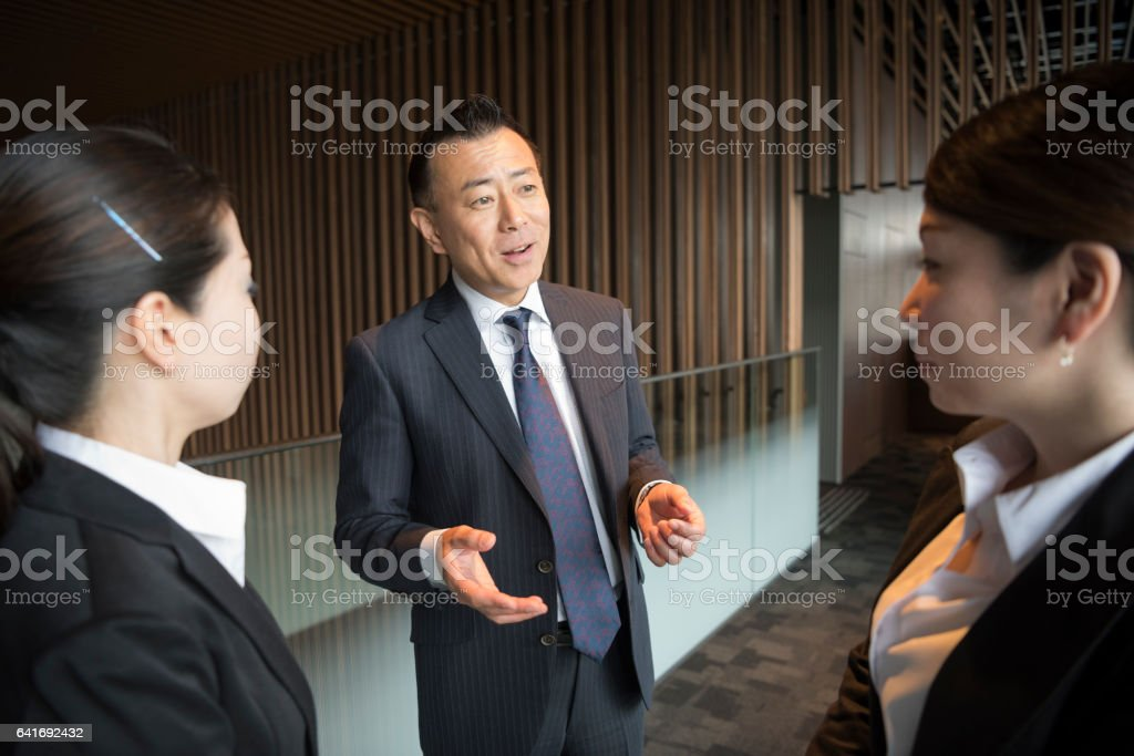 Mature Japanese businessman explaining to two female colleagues stock photo