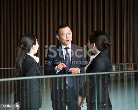 Three Japanese business people in meeting, man explaining to two women