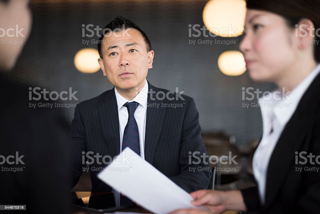 Mature Japanese businessman with female colleagues stock photo