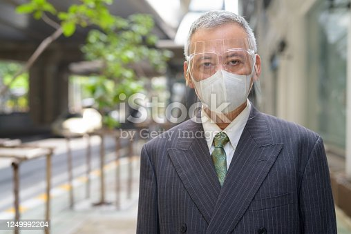 Portrait of mature Japanese businessman with mask and face shield for protection from corona virus outbreak in the city streets