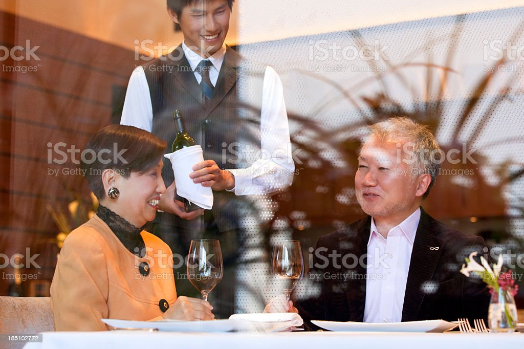 Mature Japanese couple dining at a restaurant seen through window. royalty-free stock photo