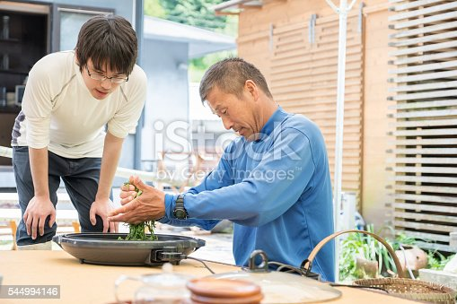 Kyoto iStockalypse.  Mature, local Japanese farmer showing his son how to dry freshly harvested, organically grown tea leaves in an electric pan and roll them.  They are in the backyard of a home in Nara, Japan.