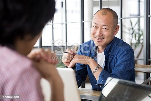 Portrait of mature Japanese Asian male in discussion with colleague at office meeting.