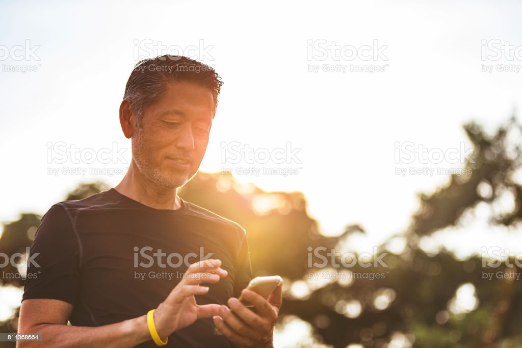 Mature Japanese man using his smart phone early in the morning during his walk stock photo