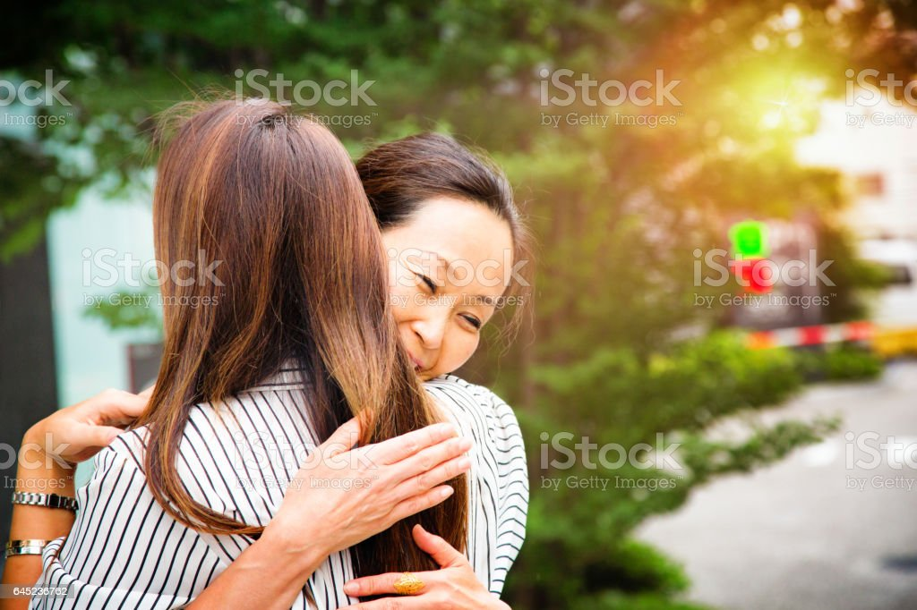 Mature Japanese woman hugs younger friend stock photo