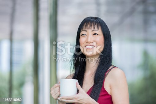 Mature Japanese woman smiles while enjoying a warm beverage outdoors in the city