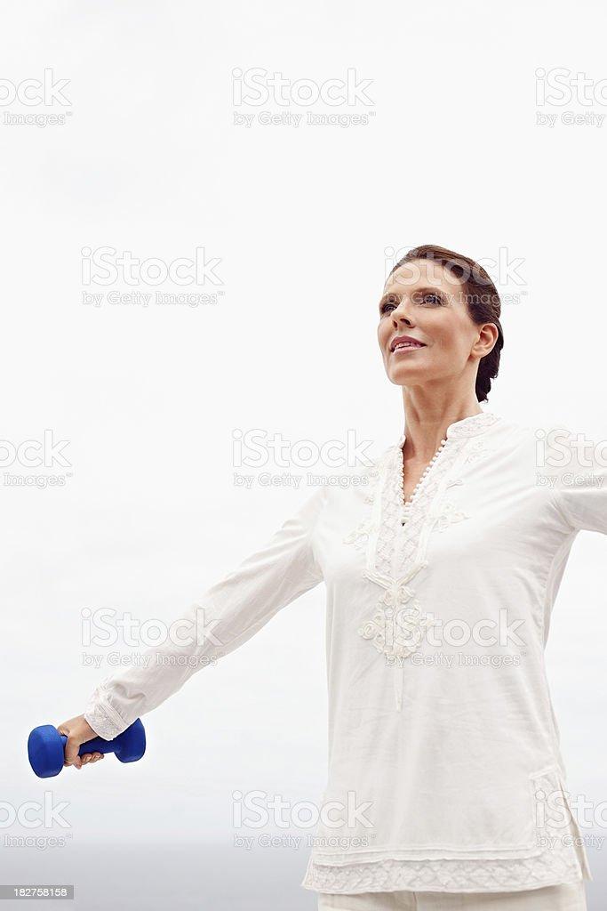 Mature lady exercising while holding dumbbell royalty-free stock photo