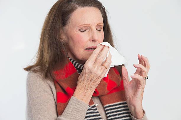 mature lady sneezing - mature woman fever on white bildbanksfoton och bilder