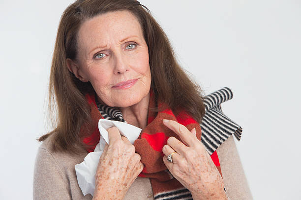 mature lady suffering from a cold - mature woman fever on white bildbanksfoton och bilder