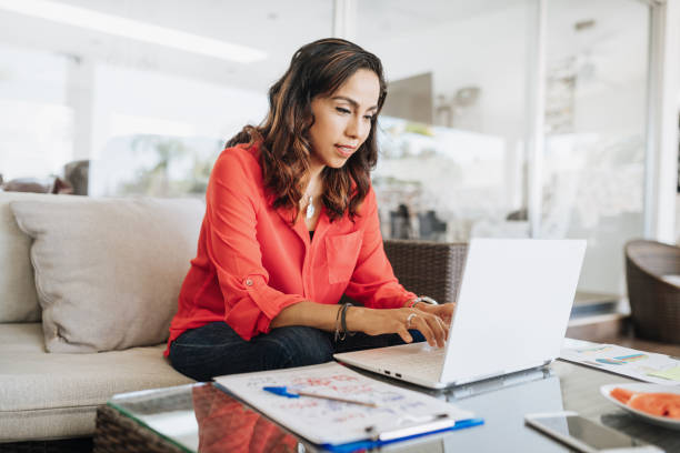 Mature Latin American businesswoman working from home Portrait of mature Latina businesswoman using computer stock pictures, royalty-free photos & images
