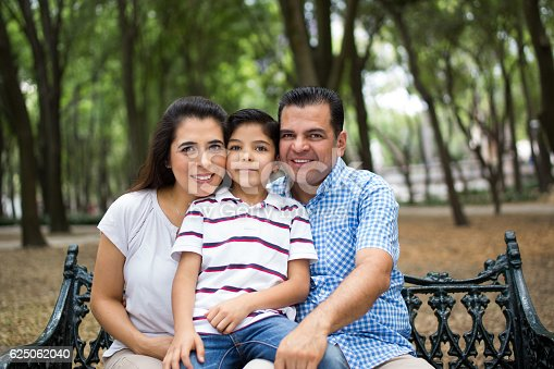 811227514 istock photo Mature latin couple sitting with son and smiling at camera 625062040