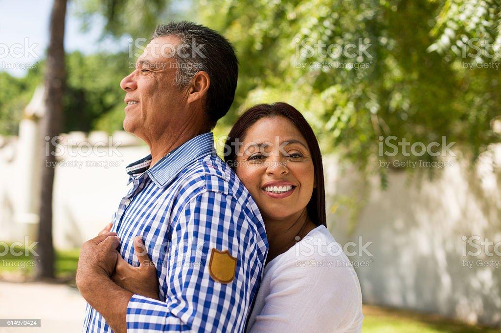 Mature latin woman embracing husband from back - Stock image .