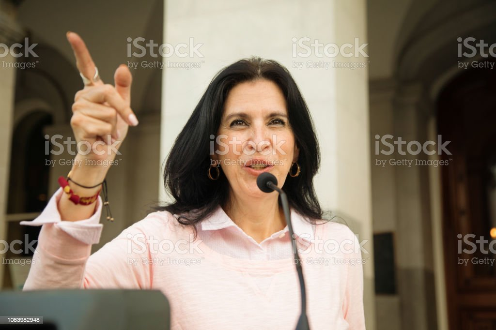 Mature Latina Female Politician Points The Way During Speech Over Microphone Stock Image