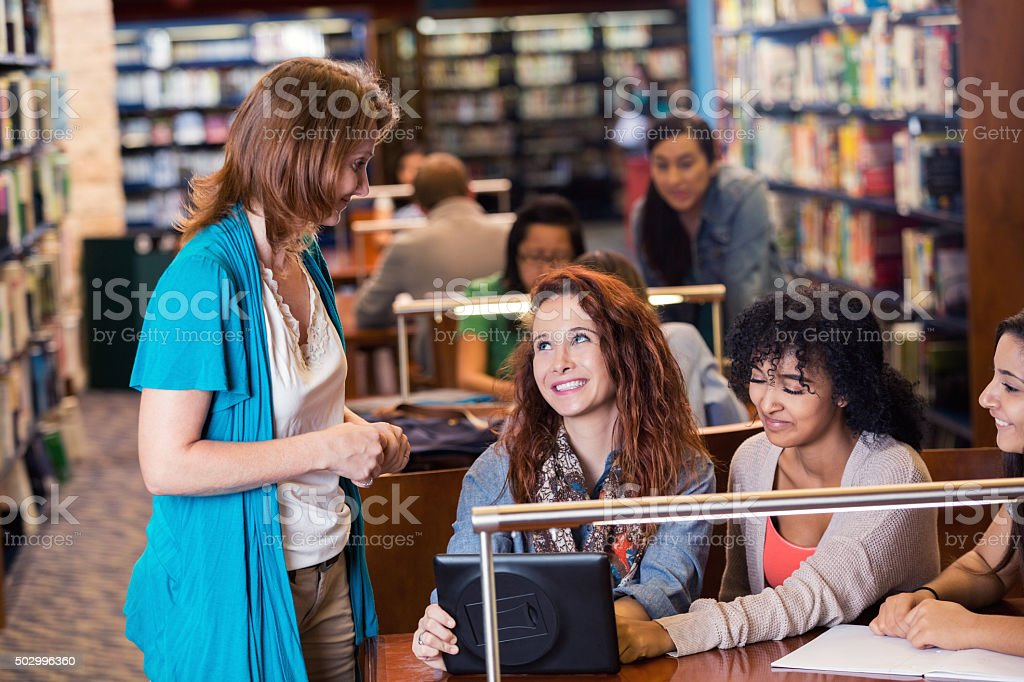 Mature librarian helps high school students in library stock photo