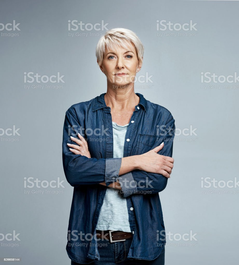 Mature lifestyle Studio portrait of a mature woman posing against a grey background 40-49 Years Stock Photo