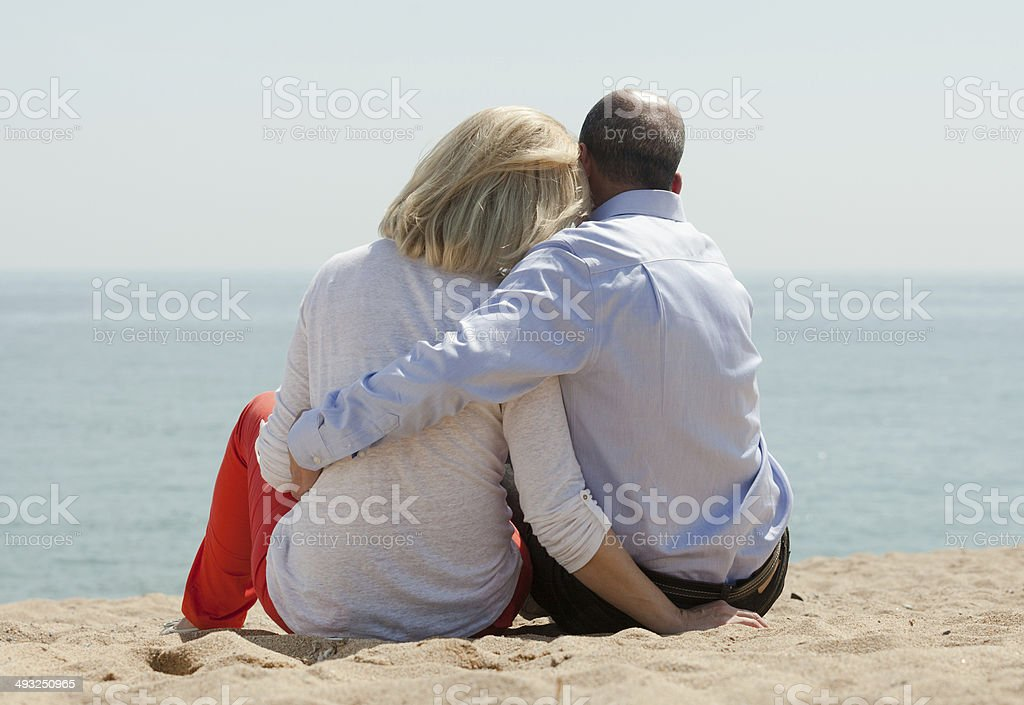 Mature lovers sitting on beach stock photo