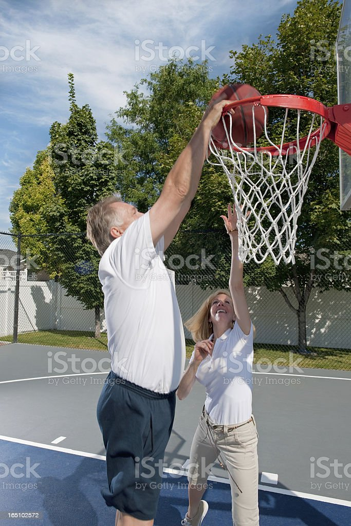 Mature Mad Dunking Ball During Basketball Game with Wife stock photo