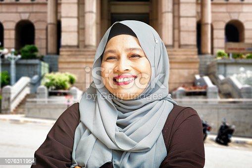 istock Mature Malaysian Asian Muslim Female civil worker portrait outdoors 1076311954