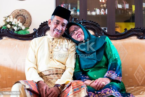 Marriage, Togetherness, Mature Couple - Elderly couple sitting together on their sofa while wearing their traditional clothing.
