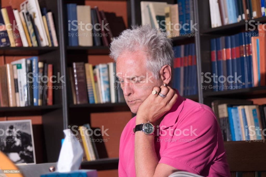 Mature male adult in home study looking intently at either book or computer royalty-free stock photo