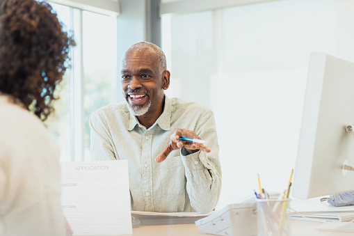 The mature adult male banker smiles and gestures while speaking to an unrecognizable female customer.
