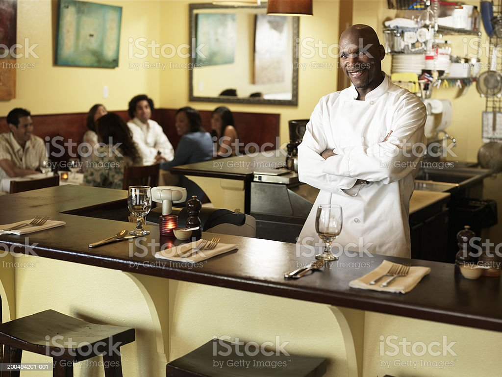 Mature male chef standing in restaurant, arms crossed, portrait royalty-free stock photo