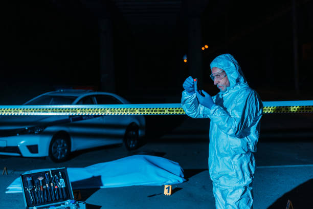 mature male criminologist in protective suit and latex gloves collecting evidence at crime scene with corpse stock photo