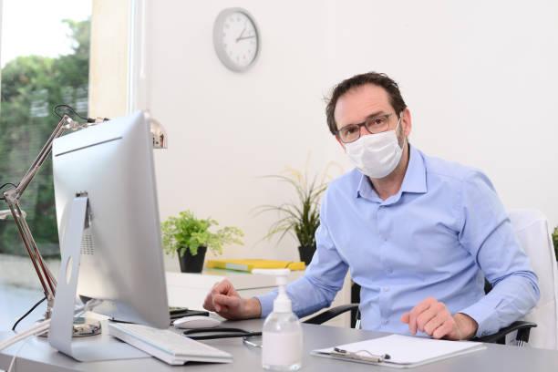 médecin masculin mature dans le bureau médical au bureau sur l'ordinateur avec le stéthoscope luttant contre le covid19 et le coronavirus - covid france photos et images de collection