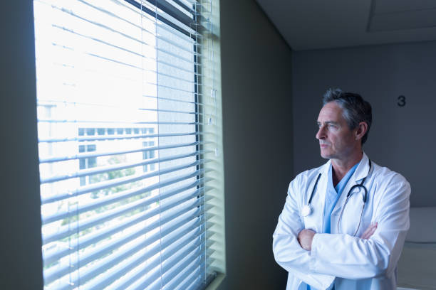 Mature male doctor looking through window in the hospital stock photo