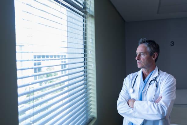 Reifer männliche Arzt schaut durch Fenster im Krankenhaus – Foto
