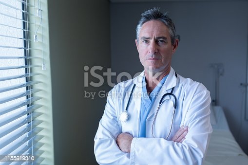 Portrait of mature Caucasian male doctor standing with arms crossed in the hospital
