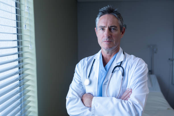 Mature male doctor standing with arms crossed in the hospital stock photo