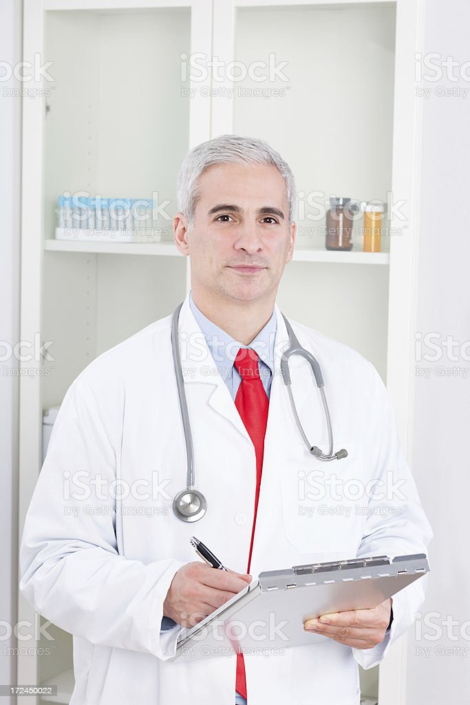 Mature Male Doctor Writing On Clipboard royalty-free stock photo