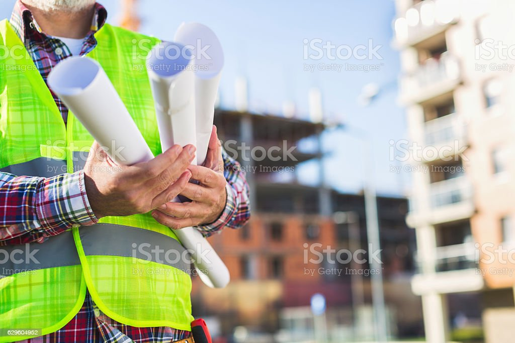 Mature male engineer holding blueprints royalty-free stock photo