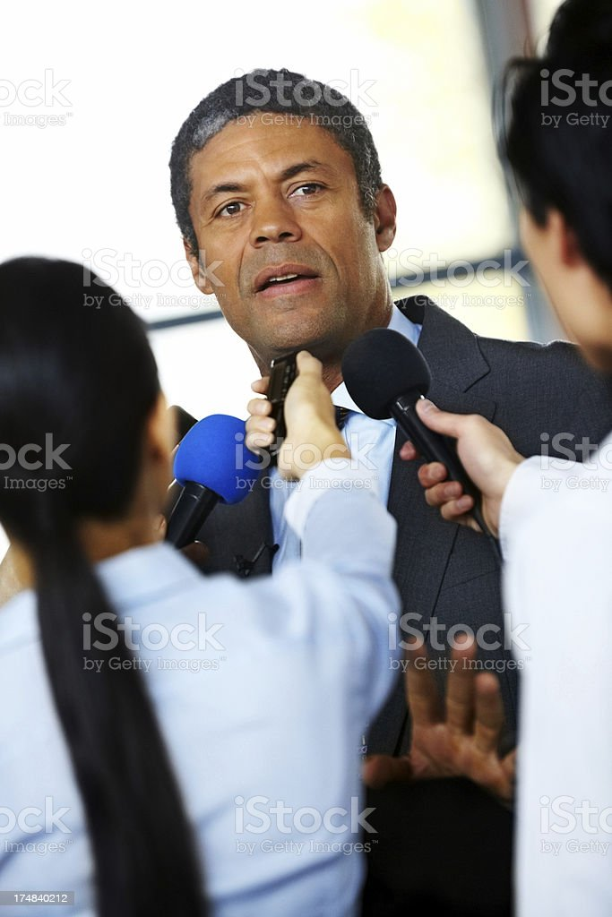 Mature male executive being questioned by journalists royalty-free stock photo