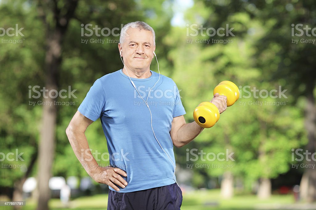 Mature male exercising with weight in a park stock photo
