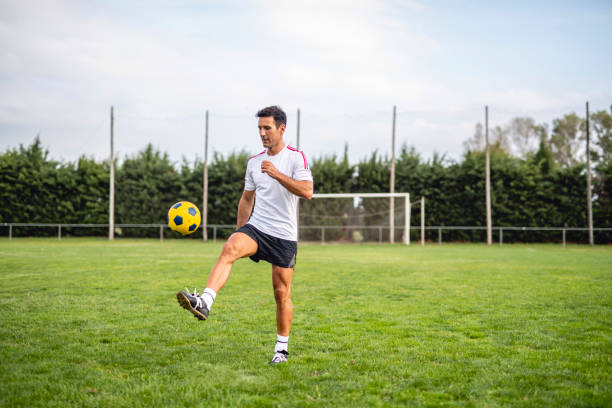 Mature Male Footballer Practicing Juggling for Ball Control stock photo