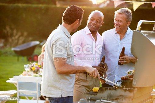 istock Mature Male Friends Enjoying Outdoor Summer Barbeque 498603382