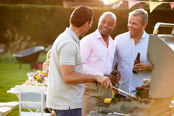 Mature Male Friends Enjoying Outdoor Summer Barbeque stock photo