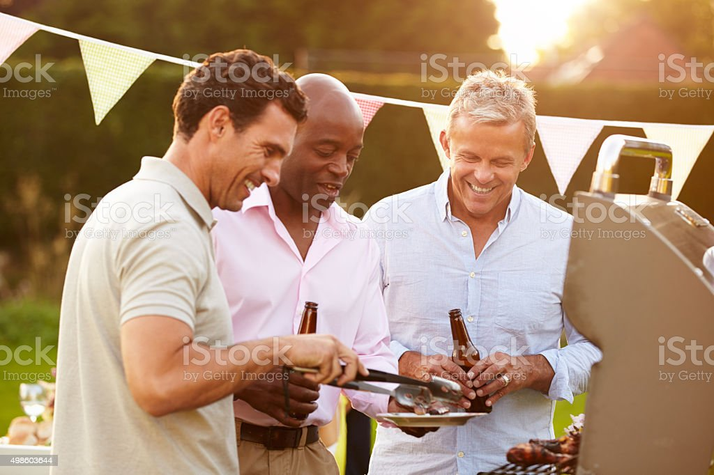 Mature Male Friends Enjoying Outdoor Summer Barbeque​​​ foto