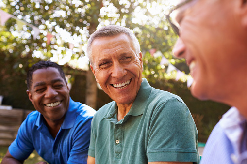 istock Mature Male Friends Socializing In Backyard Together 643324626