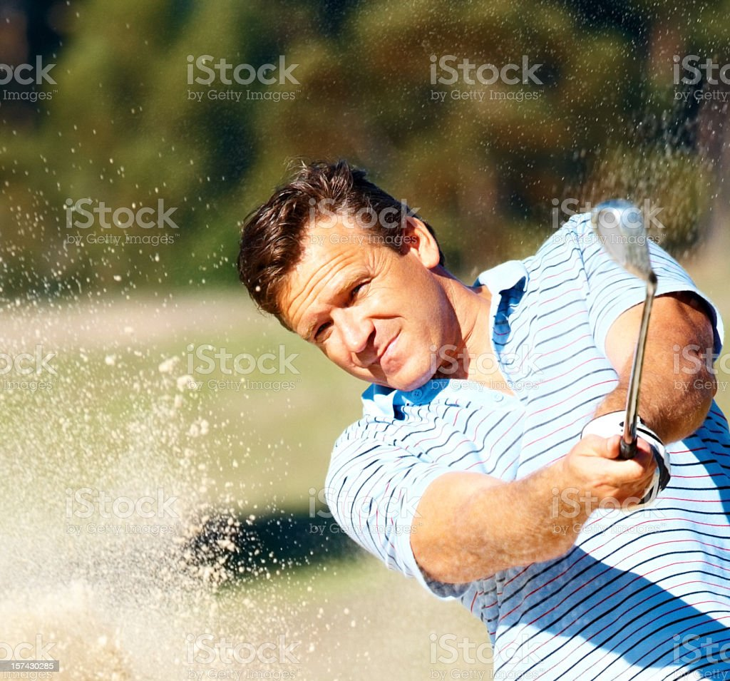 Mature male golfer hitting a bunker shot royalty-free stock photo