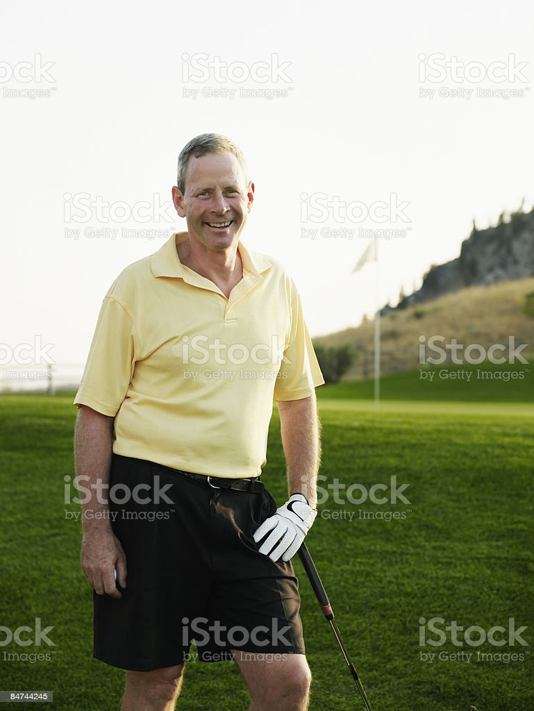 Mature male golfer next to green royalty-free stock photo