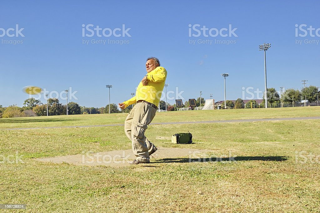 Mature Male Keeping Active with Disc Golf on Sunny Afternoon stock photo