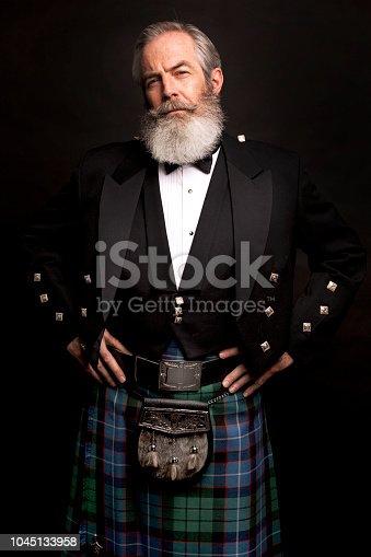 close up of senior man with grey hair and full beard, wearing scotting kilt on dark background