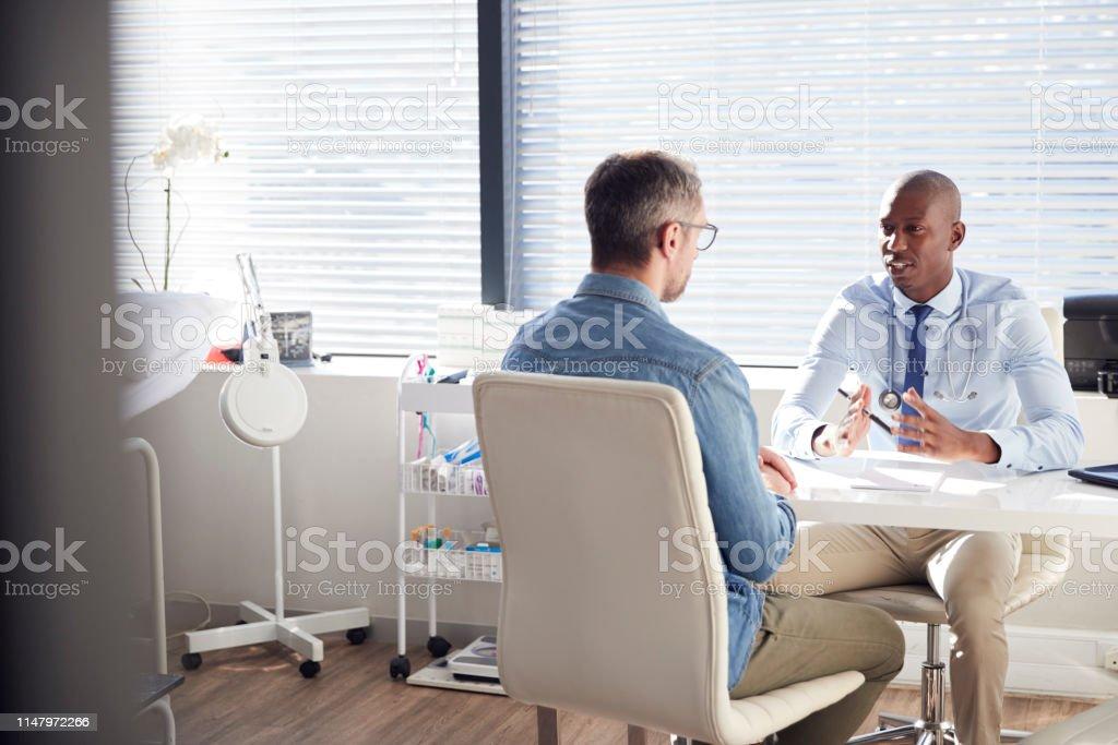 オフィスで医師と相談して成熟した男性患者 - 20代のロイヤリティフリーストックフォト