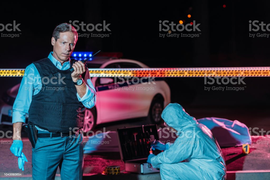 mature male police officer talking on radio set while criminologist collecting evidence at crime scene with corpse stock photo