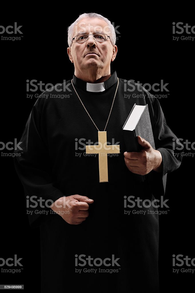Mature male priest holding a holy bible stock photo